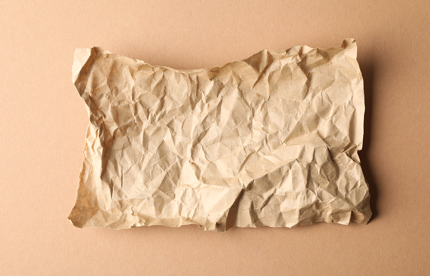 Crumpled paper on craft background, top view